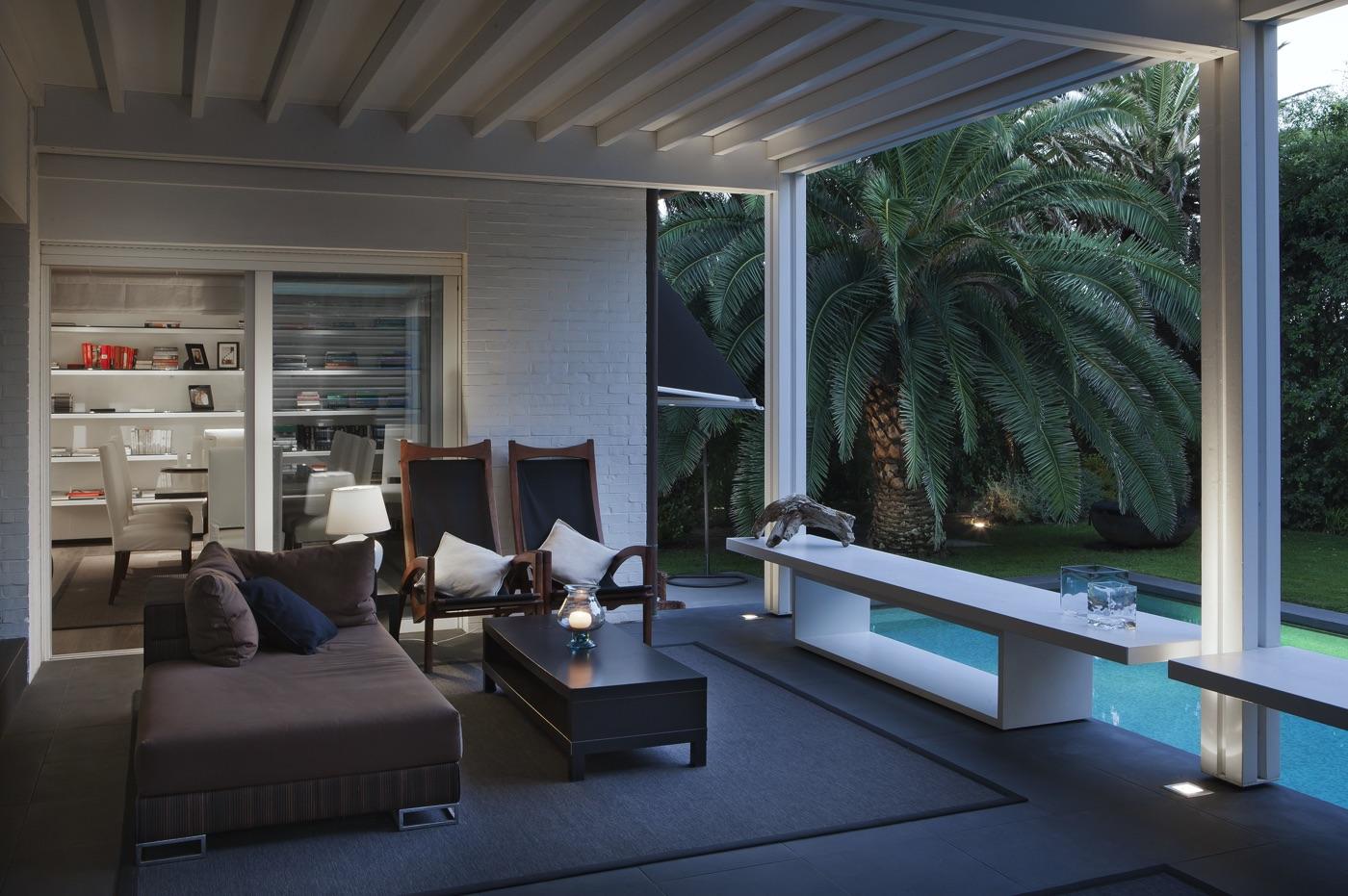 un angolo del patio vicino alla piscina con una palma sullo sfondo