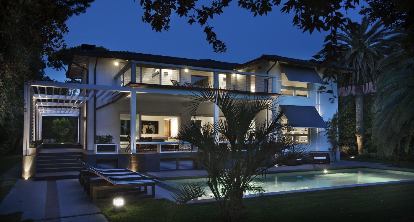 una villa con piscina fotografata di sera