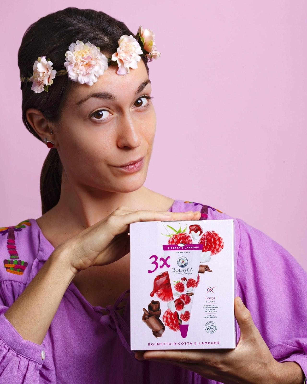 una ragazza con vestiti colorati tiene in mano una scatola di gelati Bolmea alla fragola