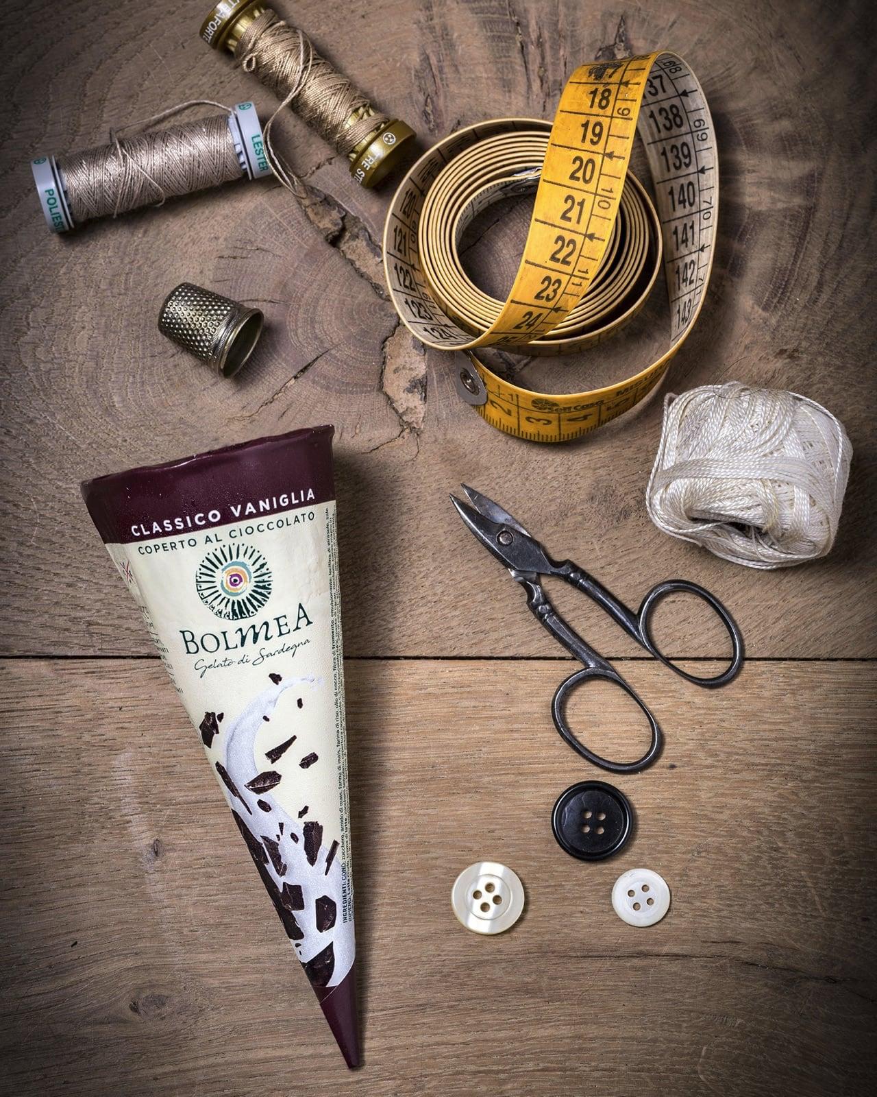 un cornetto Bolmea alla vaniglia e cioccolato su un tavolo vicino ad attrezzi da sarto: fili, un metro flessibile e dei bottoni