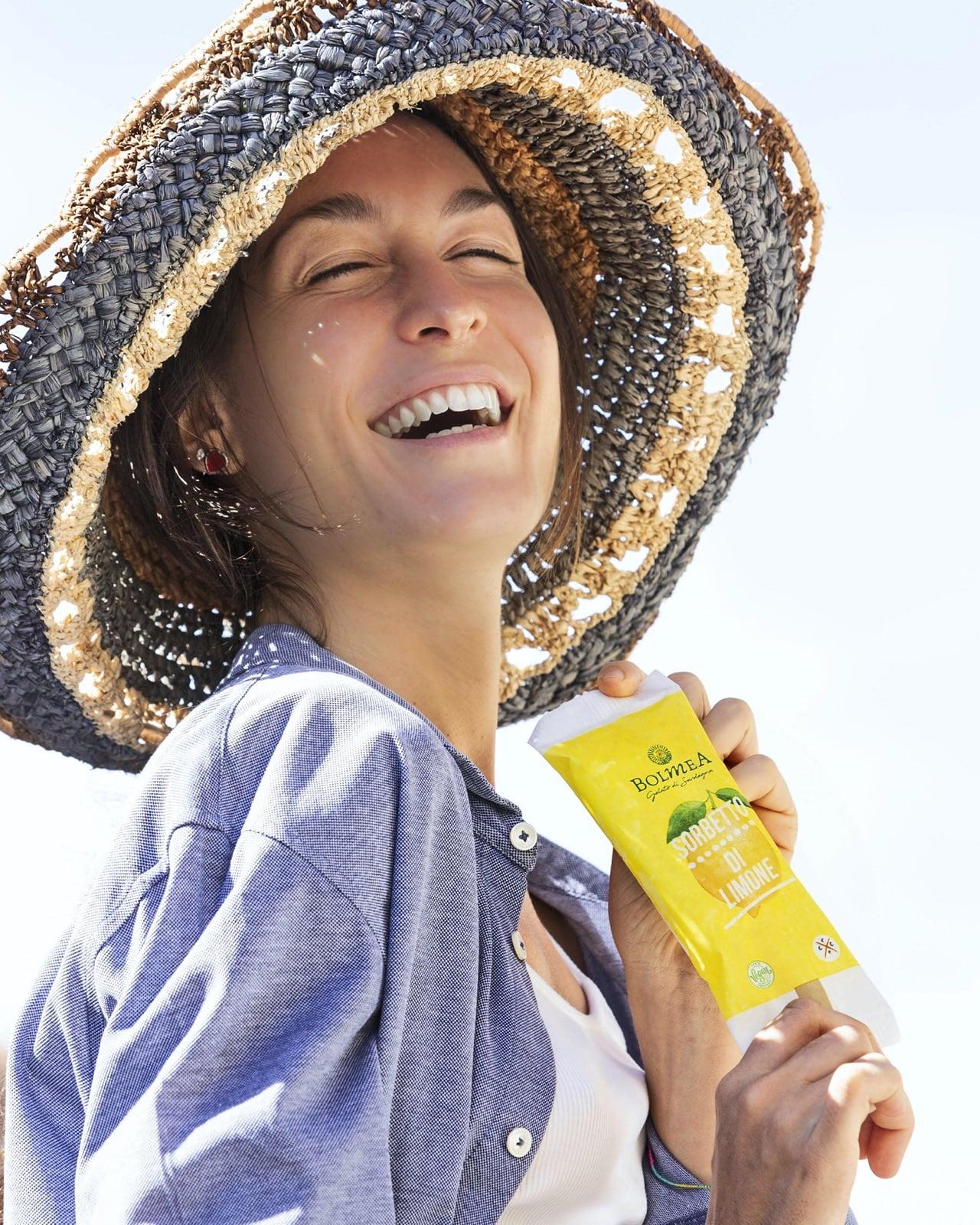 una ragazza sorride mentre tiene in mano un sorbetto al limone