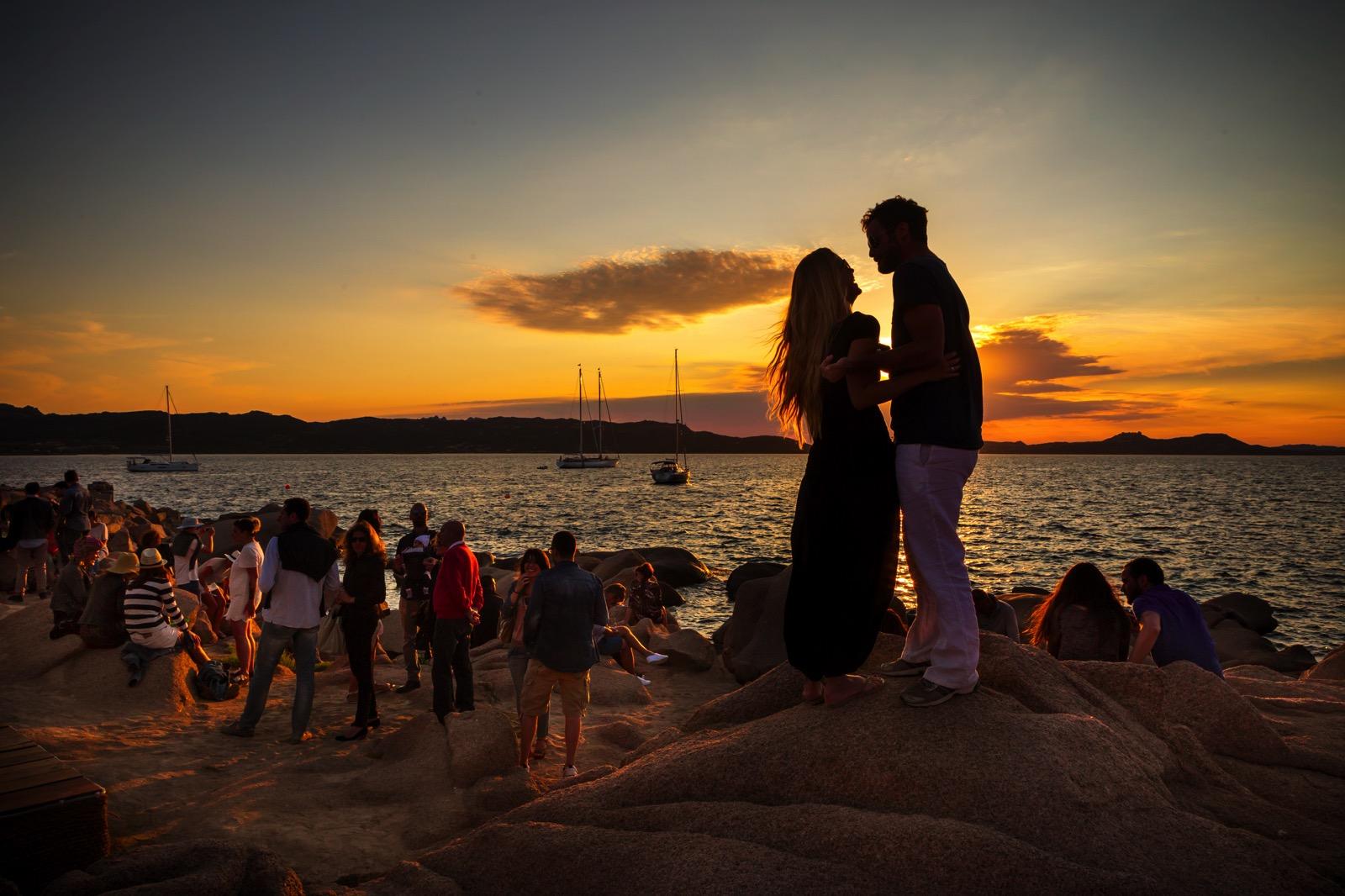 una coppia abbracciata di profilo di fronte al mare al tramonto a Baja Sardinia