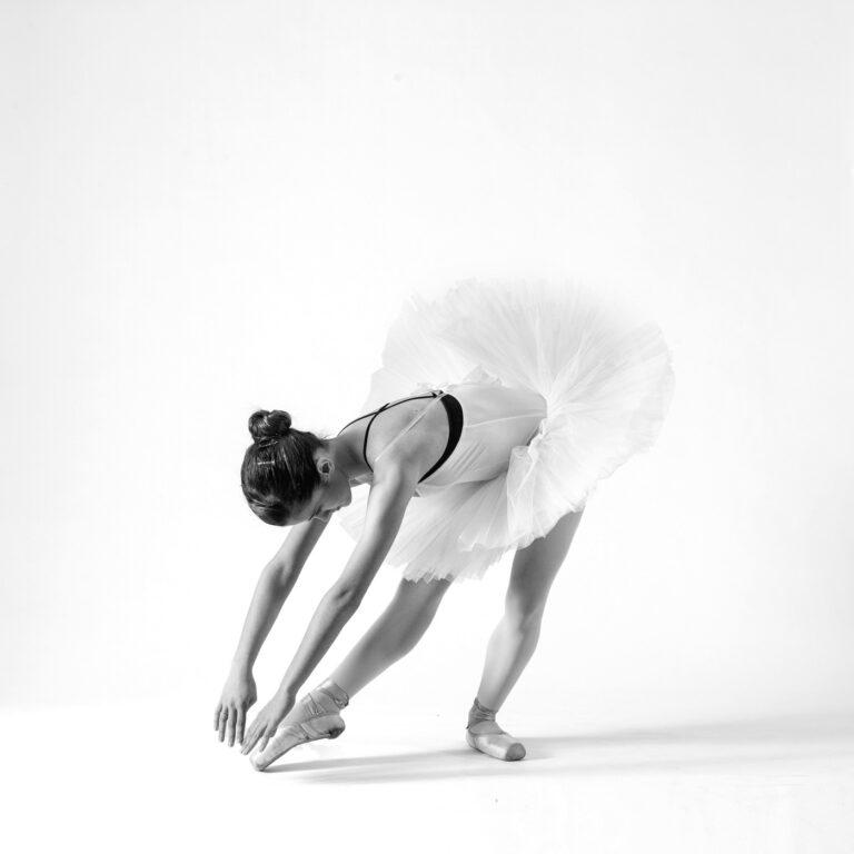 una ballerina classica in tutù si china e tocca la punta della sua scarpetta da danza