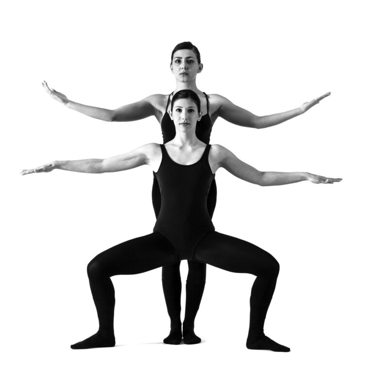 due ballerine incrociano gambe e braccia, creando l'effetto ottico di una persona con quattro gambe e quattro braccia
