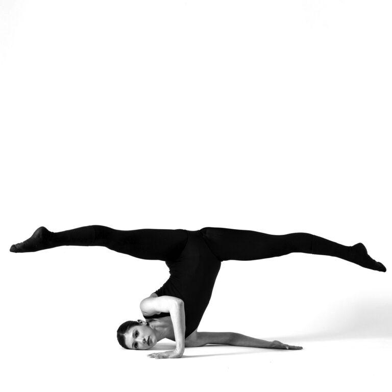 una ballerina esegue una spaccata mentre è poggiata a terra