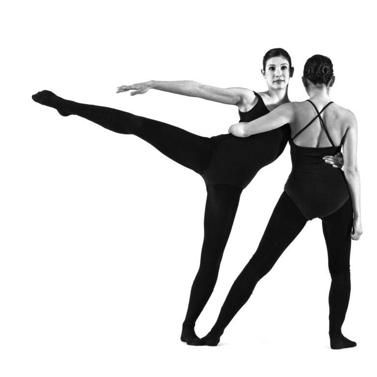 una ballerina di spalle sostiene una ballerina che allunga una gamba