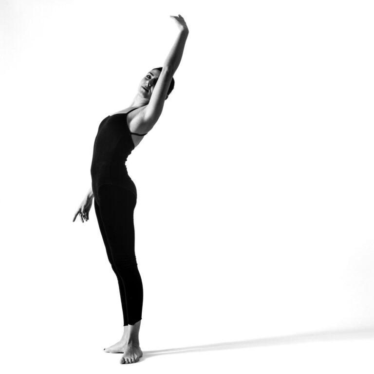 una ballerina scalza estende il braccio verso l'alto